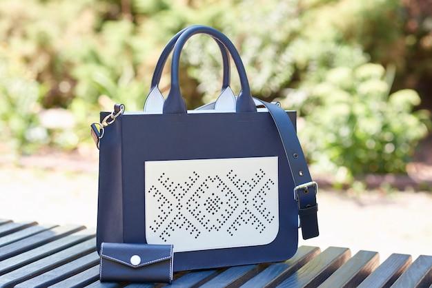 Крупный план модной женской сумки, выполненной в двух цветах: синем и белом. стоит на скамейке в парке.