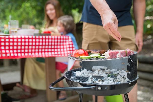 バーベキューを調理している父のクローズアップ。バーベキューグリッドに立って、新鮮な肉を調理している中年の成人男性。一緒にテーブルに座っている母と息子