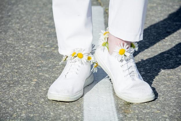 白いストリップのアスファルトの上に立っている白いスニーカーの足のクローズアップ。