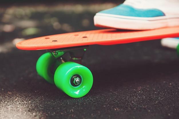 アスファルトの上のオレンジのペニースケートボードに乗って女の子スニーカーの足のクローズアップ