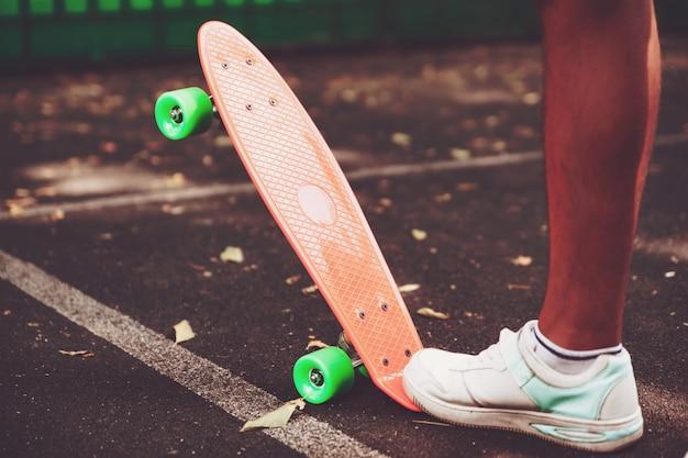 アスファルトの上のオレンジペニースケートボードに乗って男スニーカーの足のクローズアップ