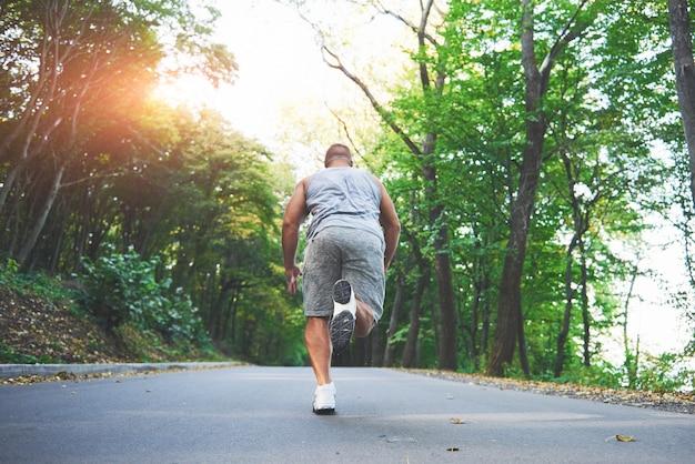 公園の道路に沿って走っている若いランナーの男の足のクローズアップ。