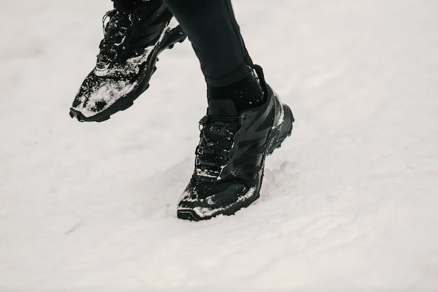 야외에서 눈 속에서 달리는 발을 닫습니다. 운동복, 겨울 피트니스, 운동화