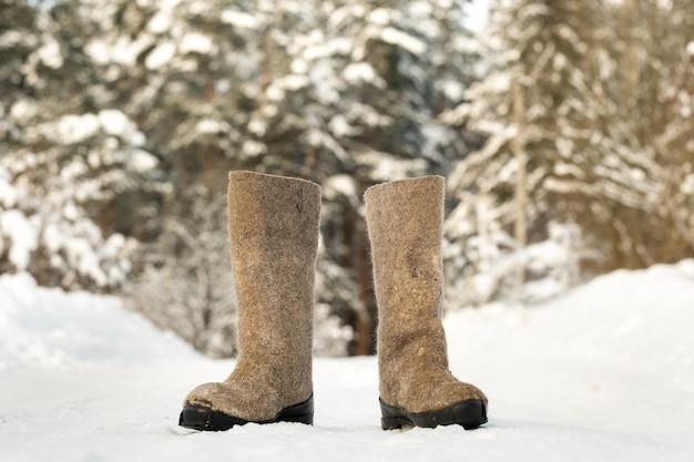 Закройте валенок, стоя в снегу.