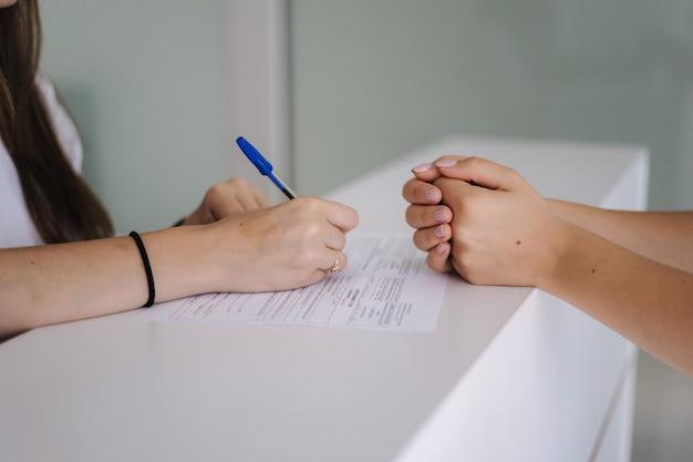レシピを書いている間、女性と医師の手をテーブルにクローズアップ