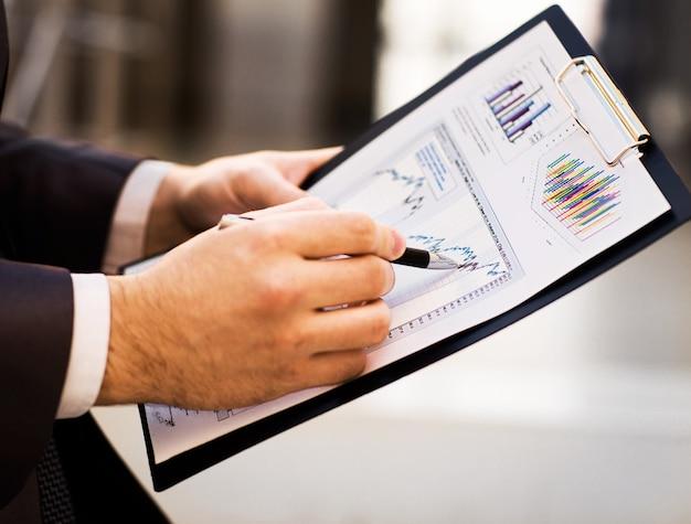 Крупный план женских и мужских рук, указывающих на деловой документ во время его обсуждения