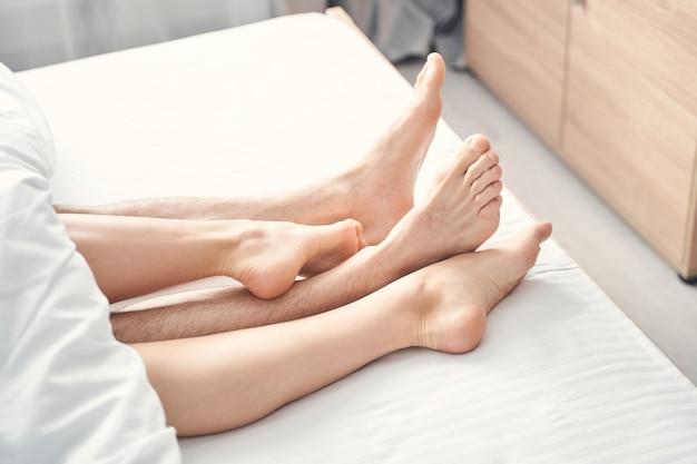 Крупным планом женские и мужские ноги, торчащие из-под одеяла в спальне