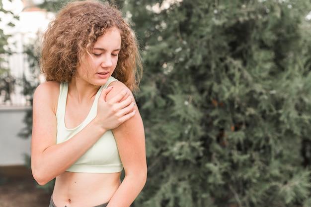 Крупный план женщины-спортсмен, имеющий боль в плече