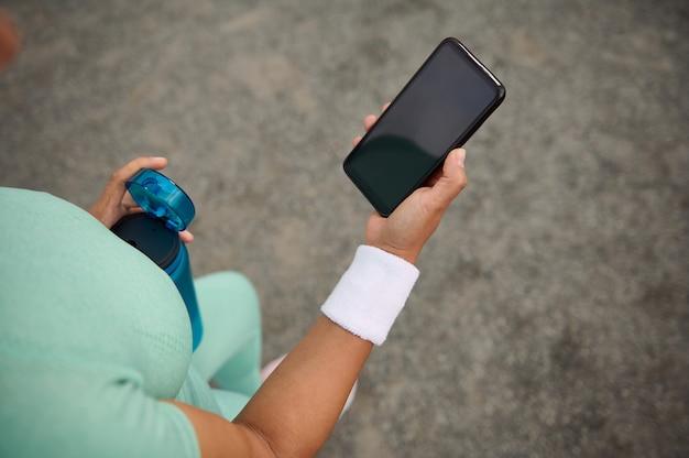 女性アスリートのクローズアップ、広告用のコピースペースと空の空白の黒い画面でスマートフォンを持っているスポーツの女性の手