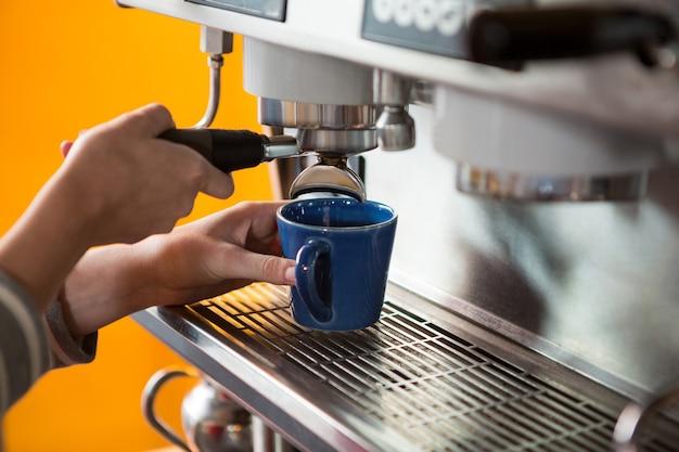 카페테리아에서 기계로 커피를 준비하는 여성 바리 스타의 근접