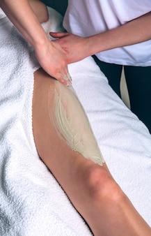 スパの女性の足に粘土処理を適用している女性の美容師のクローズアップ。医学、ヘルスケア、美容のコンセプト。