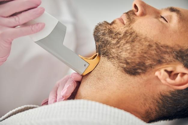 레이저 장치로 남성 목에서 원치 않는 머리카락을 제거하는 살균 장갑에 여성 미용사의 손을 닫습니다