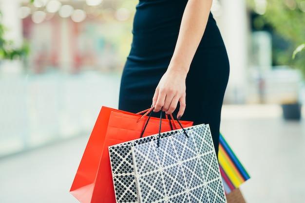 Закройте клиента женского пола в черной юбке, наслаждаясь покупками в торговом центре.