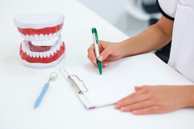 コピースペースでクリップボードに何かを書いている女性の歯科医の手のクローズアップ