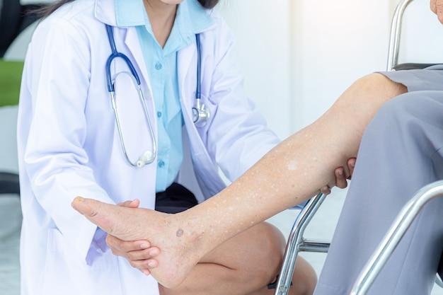 휠체어에 앉아 있는 동안 고위 여성의 다리를 검사하는 여성 의사의 클로즈업. 노인 환자 치료 및 건강 관리, 의료 개념.
