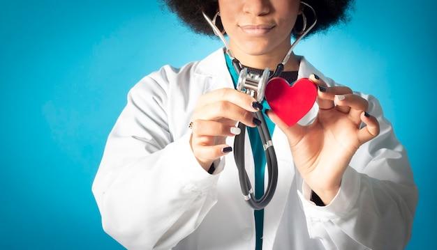 Stocope로 호위하면서 종이 심장을 들고 있는 여성 의사의 손을 클로즈업