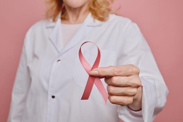 스튜디오, 유방암 인식 개념, 복사 공간에서 분홍색 배경에 포즈를 취하는 동안 카메라에 핑크 리본을 들고 여성 의사의 닫습니다