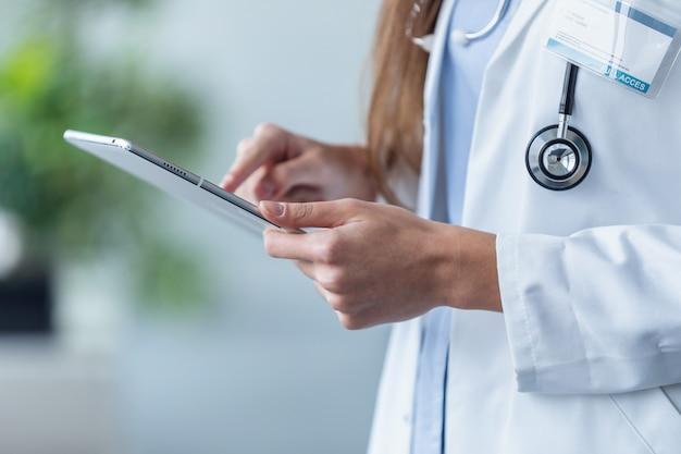 Крупным планом женщина-врач с помощью своего цифрового планшета в офисе.