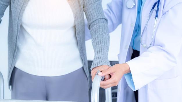 Крупным планом женщина-врач в медицинской маске, поддерживающая старшую женщину с помощью ходунка. уход за пожилыми пациентами и здравоохранение, медицинская концепция.