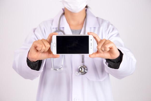 白い背景で隔離の電話で女医のクローズアップ。新しい正常。