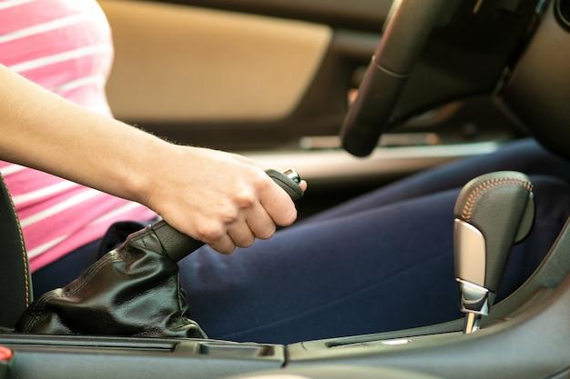 車の中でハンドブレーキを持っている女性ドライバーの手のクローズアップ