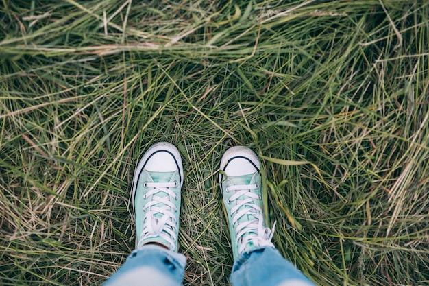 Крупный план женских ног в холщовых кроссовках, стоящих на траве.