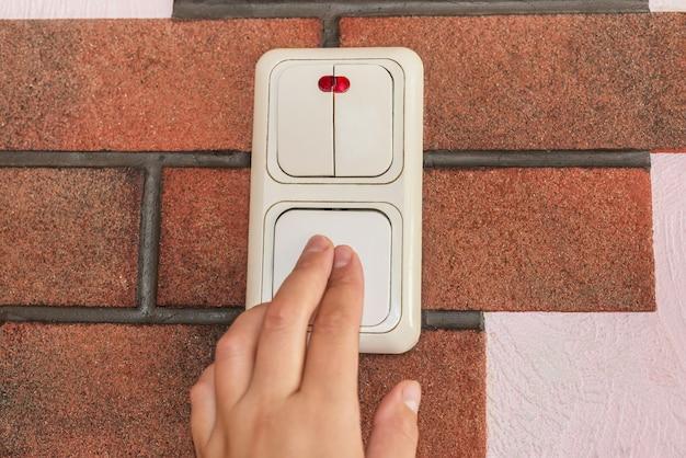 女性の指のクローズアップは、自宅の照明スイッチでオフになっています。電力、エネルギー、電気の節約、コピースペース。