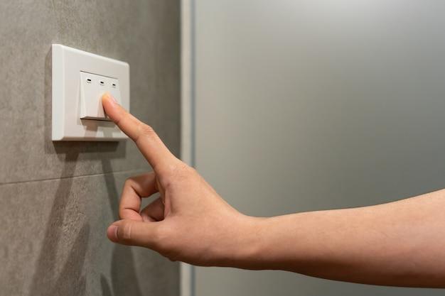 Крупным планом женский палец выключается на выключателе освещения