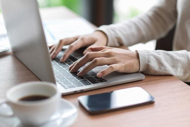Крупным планом женские пальцы, печатающие на клавиатуре ноутбука со смартфоном и кофе на деревянном столе