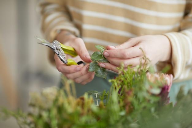ワークショップ、コピースペースで花の組成物を配置しながら女性の花屋挿し木植物のクローズアップ