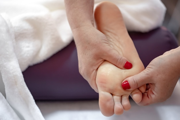 Крупным планом женские ноги в руках массажист расслабляющий массаж ног в спа-салоне.