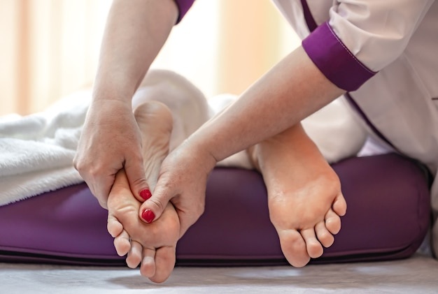 스파 살롱에서 편안한 발 마사지를 받는 안마사의 손에 여성의 발을 가까이 하세요.