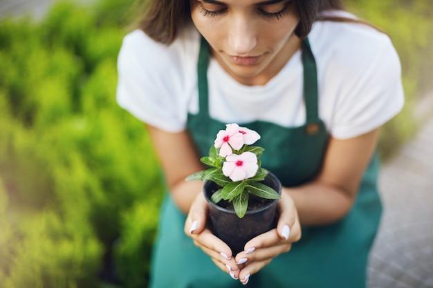 ポットに花を持っている女性の庭師のクローズアップ。ケアのコンセプト。