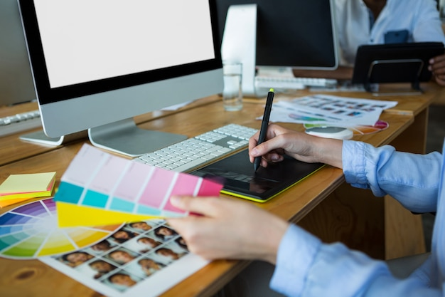 데스크에서 그래픽 태블릿을 사용하여 여성 그래픽 디자이너의 근접