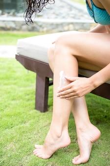 脚に日焼け止めを塗っている女性の手のクローズアップ
