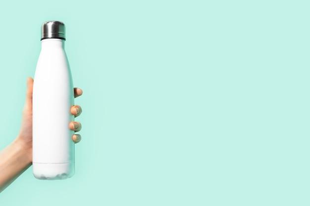 コピースペースでシアン、青、アクアメンテ色の背景に分離された、白の再利用可能な鋼、エコサーモウォーターボトルを持っている女性の手のクローズアップ。