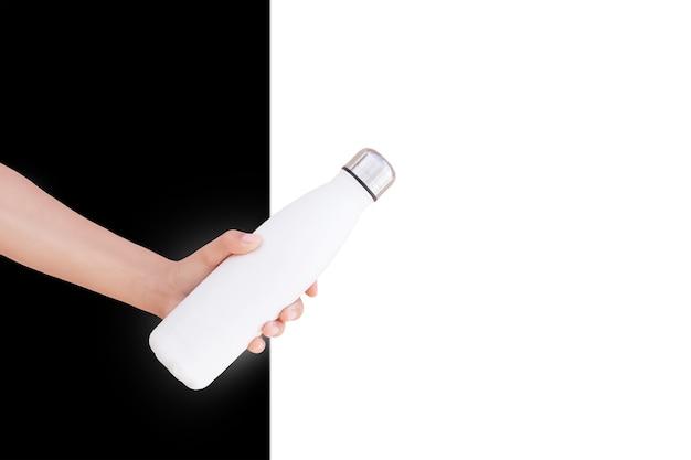 黒と白の壁の背景に、鋼のサーモエコボトルを持っている女性の手のクローズアップ。
