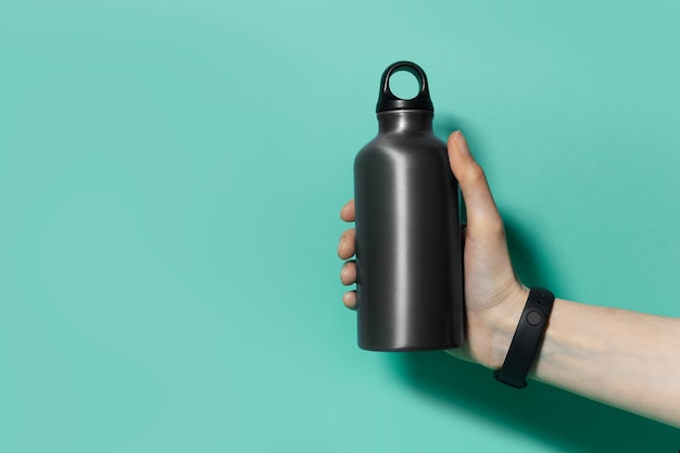 블랙의 알루미늄 재사용 가능한 열 물병을 들고 여성 손 클로즈업