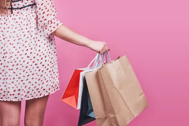 Крупный план женской руки, держащей красочные хозяйственные сумки на розовом фоне.