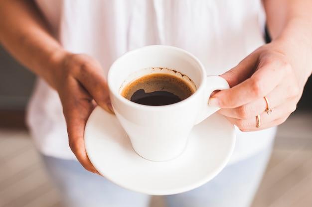 Крупным планом женская рука держит вкусную чашку кофе