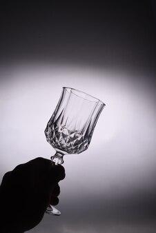 Закройте женской руки, держащей пустой чистый прозрачный стеклянный кубок против белой стены.