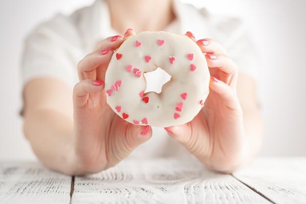 Крупным планом женская рука держит глазированный пончик
