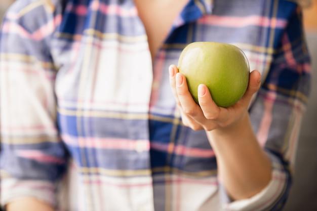 Закройте женской руки, держащей зеленое яблоко, здоровую пищу, фрукты. диетическое органическое питание, натуральные и свежие продукты, богатые витаминами. готовится, делает предложение кому-то. copyspace.