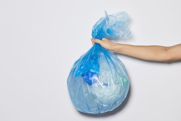 흰색 배경에 대해 쓰레기와 함께 패키지를 들고 여성 손 클로즈업