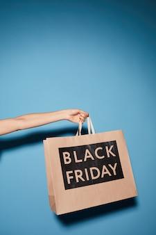 Крупный план женской руки, держащей бумажный пакет из черной пятницы в магазине