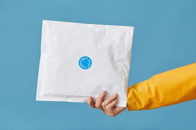 Крупный план женской руки, держащей посылку, упакованную в белую бумагу, изолированную на синем