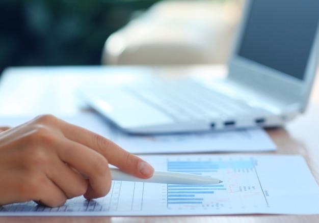비즈니스 문서 위에 펜을 들고 있는 여성의 손 클로즈업