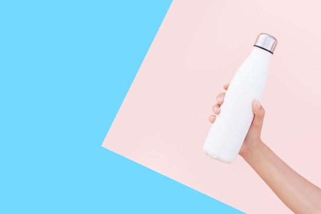 再利用可能な鋼の熱水ボトルを持っている女性の手のクローズアップ