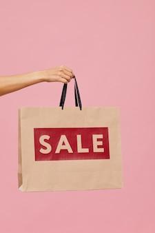 Крупный план женской руки, держащей распродажу хозяйственную сумку на розовом фоне