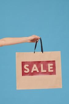 Крупный план женской руки, держащей хозяйственную сумку из продажи на синем фоне